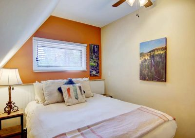 Bedroom with orange accent wall and photo of Fish Creek Falls.
