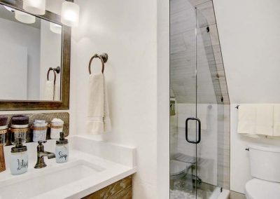 Bathroom with white walls and walk in shower.