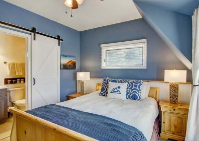 Queen size bed decorated with blue accents and blue walls.