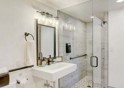ADA compliant bathroom with white walls and gray tiles.